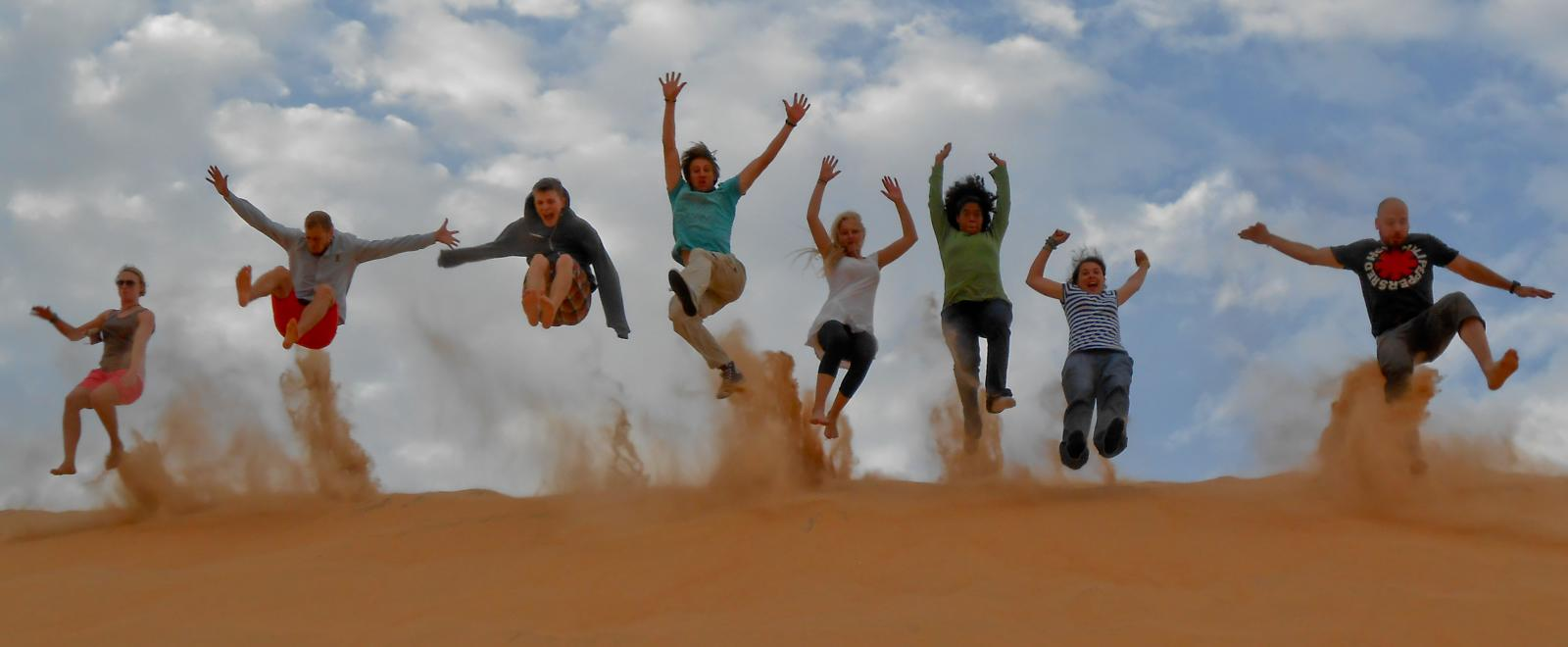 A group of volunteers jumping over sand dunes in Senegal